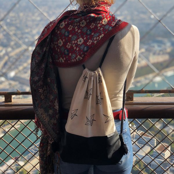 Young girl with drawstring bag on top of eiffel tower