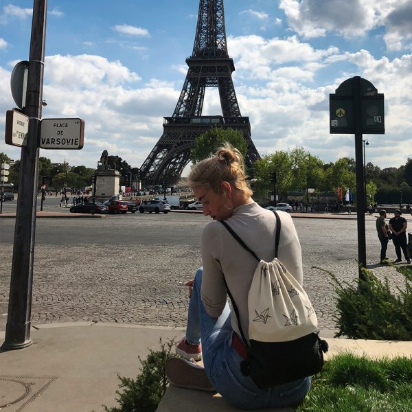 Young girl with drawstring bag in front of eiffel tower